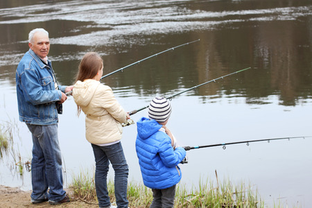 Grandfather and grandchildren are fishing photo