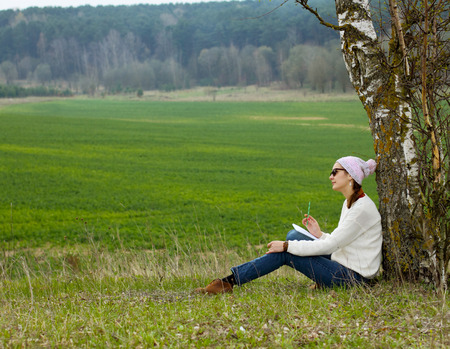 Ordinary hipster girl writing in a notebook outdoors photo