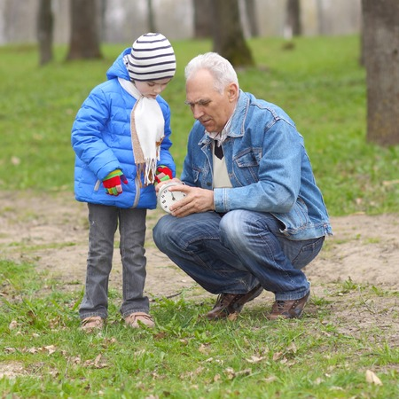 Grandfather and grandson study time on the old clock photo