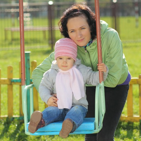 Mother and daughter playing on the playground outdoors on a sunny day photo