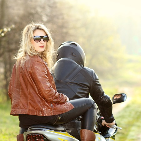 Biker girl with sunglasses sitting on motorcycle Imagens