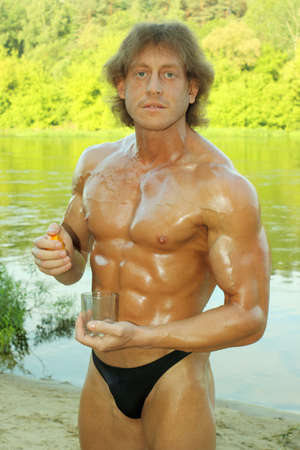 male fitness model bodybuilder squeezes out orange juice in a glass photo