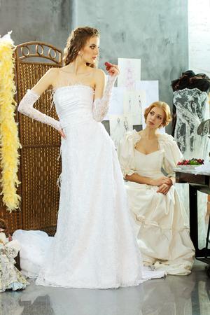 design studio: Girl tries on a wedding dress in the clothing design studio
