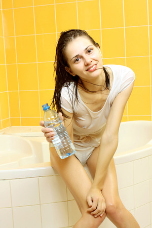 sauna nackt: Nude sexy M�dchen in nassen T-Shirt trinkt Wasser aus einer Flasche in der Wanne
