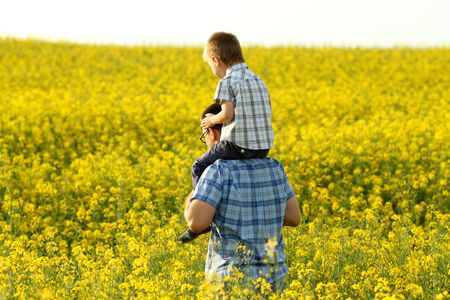 happy family in a field of yellow flowers photo