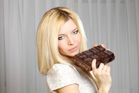 easy going: Nice natural cute blonde girl eating a large bar of chocolate