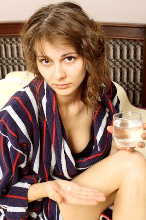 woman in a bathrobe suffering from a headache