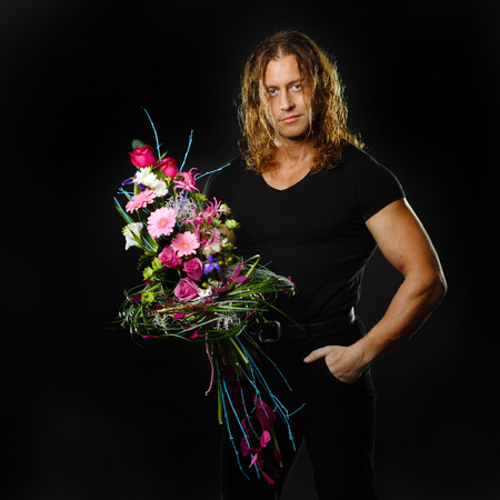 manly muscular man with long hair holds in hands a bouquet of flowers design. photo