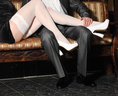 prostituta: chica en medias blancas seduce a hombre en el interior. Abraza los hombres y mujeres en un restaurante. Foto de archivo