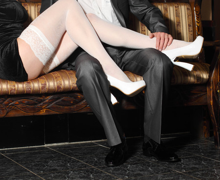 stocking feet: girl in white stockings seduces man indoors. Embrace the men and women in a restaurant.
