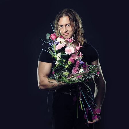 manly muscular man with long hair holds in hands a bouquet of flowers design photo