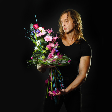 manly muscular man with long hair holds in hands a bouquet of flowers design. Black background. photo
