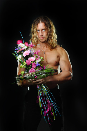 The long-haired male fitness model shirtless holding a bouquet of flowers. photo