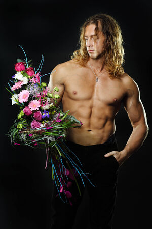 The long-haired male fitness model shirtless holding a bouquet of flowers.