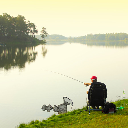 Fisherman fishing. Feeder sport. A fisherman catches a fish in the morning at sunrise in the fog photo