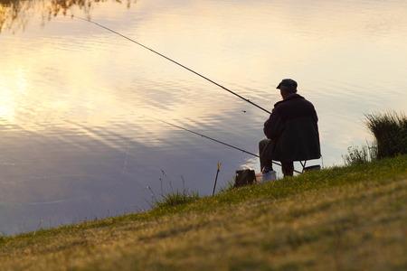 pescador: Pesca del pescador. Un pescador captura un pez en la ma�ana Foto de archivo
