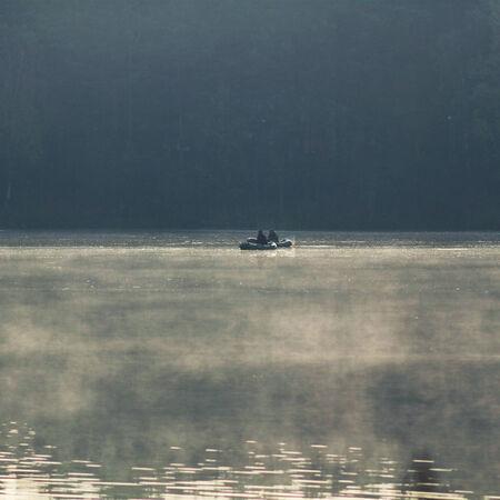 The fishermen on the boat in the fog. Fishermen in the morning mist photo