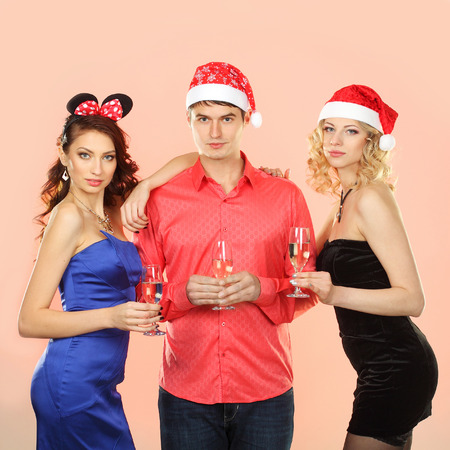 Two young attractive women kissing man. company enjoys Christmas.  Portrait of modern young people enjoying themselves at Christmas party. photo