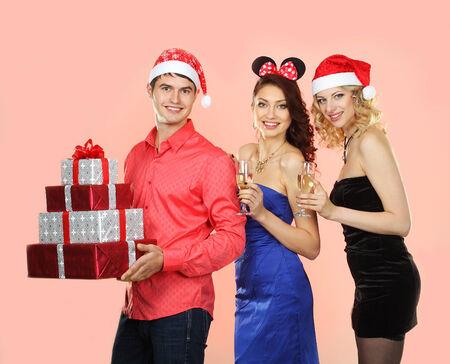 man in santa hat gives a lot of bright gifts for Santa girls photo