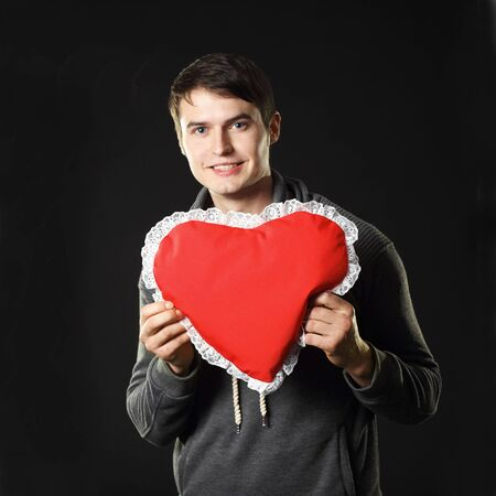 Ordinary handsome man with a heart-shaped pillow. On a black background. photo