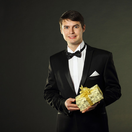 gigolo: nice handsome man in a tuxedo gives a gift. On a black background. Stock Photo