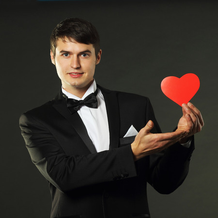 gigolo: nice handsome man in a tuxedo with a red paper heart. On a black background. vintage toning Stock Photo