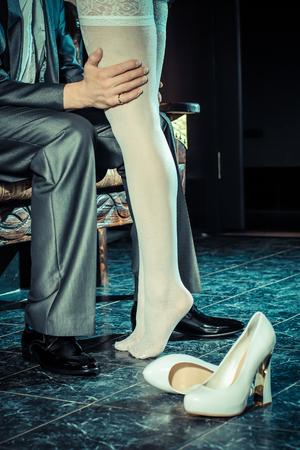 white stockings: girl in white stockings seduces man indoors Stock Photo