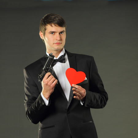 Nice handsome man in a tuxedo with red paper heart and with a gun.