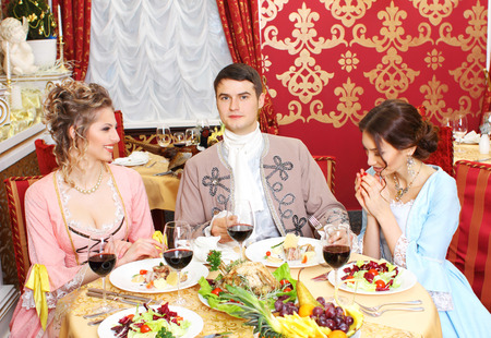 richly: Company in the historic vintage clothing have fun in a richly served restaurant.