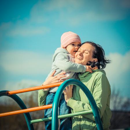 madre soltera: Madre e hija jugando en el patio de recreo al aire libre en un día soleado