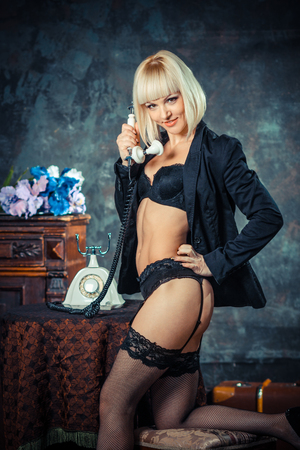 pinup girl: Girl in lingerie and stockings talking on vintage phone.