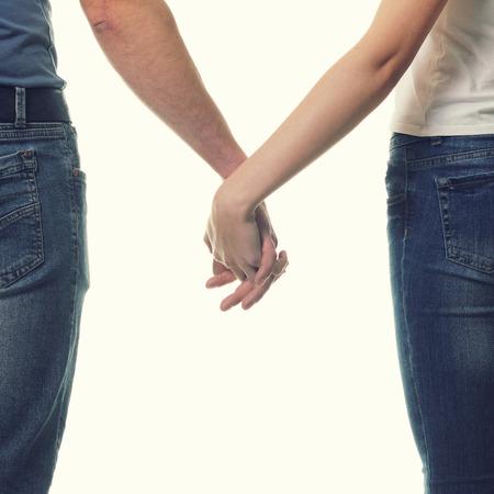 affectionate action: Pareja cogidos de las manos felices. Detalle de la joven pareja cari�osa de la mano sobre blanco. Foto de archivo