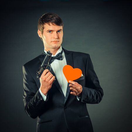 gigolo: nice handsome man in a tuxedo with red paper heart and with a gun. On a black background. vintage toning
