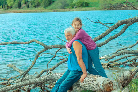open spaces: Grandfather and granddaughter are dreaming in nature. Grandfather and granddaughter enjoy the open spaces in nature. Stock Photo