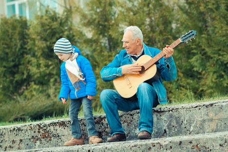 grandson: Grandfather and grandson playing guitar outdoors