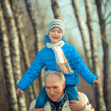 indulge: Grandfather and grandson indulge. Grandfather Carrying Grandson On His Shoulders. The grandfather makes movies on old movie camera.
