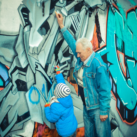 Grandfather and grandson paint graffiti on the wall