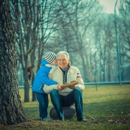 abuelos: Abuelo y nieto leyendo un libro al aire libre