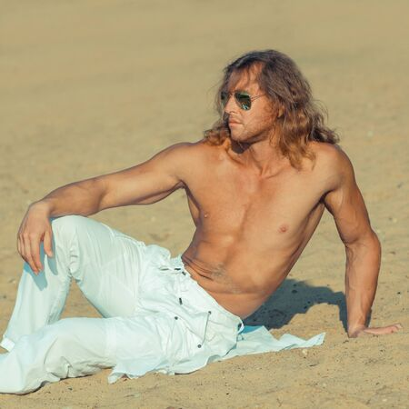 beach hunk: Fitness model man with long hair and wearing sunglasses posing on the beach