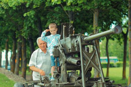 civilians: Grandfather shows for his grandson old military artillery gun Stock Photo