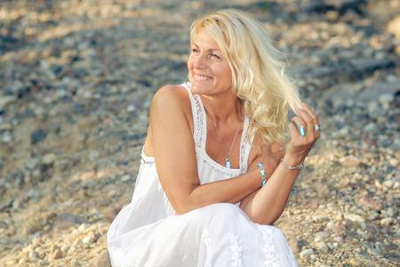 romantisches Porträt einer schönen ältere Frau. Ältere schöne Blondine in einem weißen Kleid Spaziergänge auf der Straße