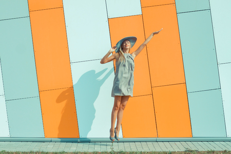 hollow wall: beautiful happy girl in a bright dress and a long hollow hat having fun near the orange wall. Girl jumping for joy