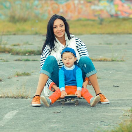 sport fitness: Mother and son on a skateboard. young mother teaches her little boy to ride a skateboard