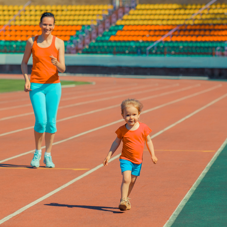 Mother and little daughter running around the stadium. Child runs away from mom at the stadium. Banco de Imagens