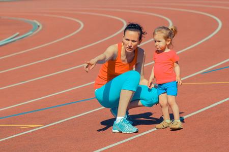 child sport: Mother and little daughter running around the stadium. Child runs away from mom at the stadium. Stock Photo