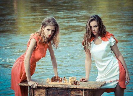 rivals rival rivalry season: petite girls in a dress playing chess at a vintage table near the river. Vintage toning