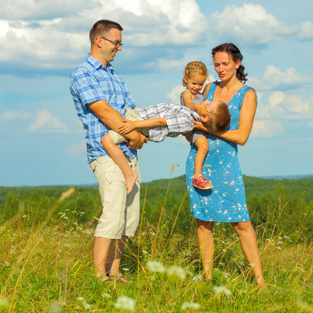mam: happy young family of four having fun on the top of a hill