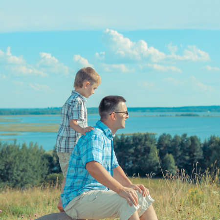 happy family nature: Dad and son happy on a hill in a landscape and open space. happy family against a landscape background. Outdoors on a background of sky and clouds. Stock Photo