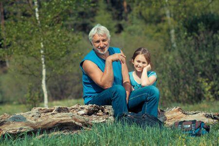 魅力的な場所で彼の孫娘と祖父。彼の孫娘とのキャンプ旅行に歳の男性写真家。