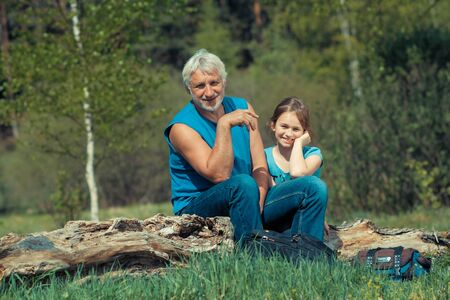 suo: Grandfather with his granddaughter travel at attractive places. Old man photographer on a camping trip with his granddaughter. Archivio Fotografico